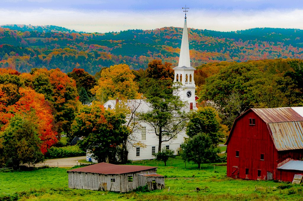A white church amongst fall color trees in Vermont