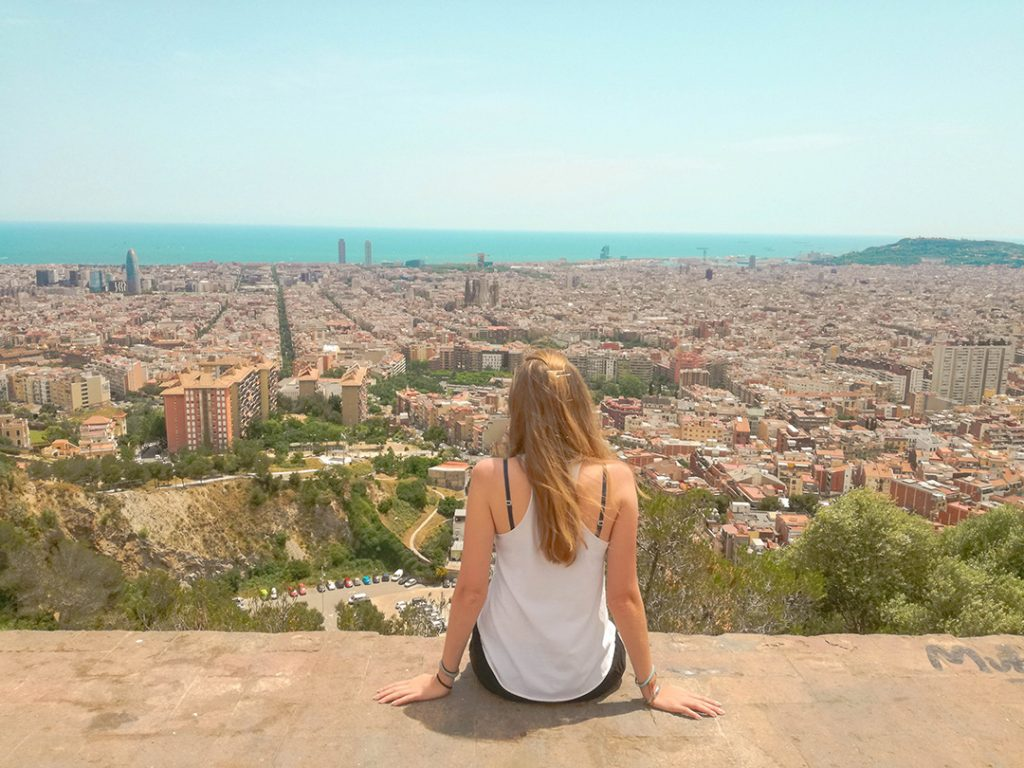 A girl looking out at a birds-eye view of Barcelona, Spain