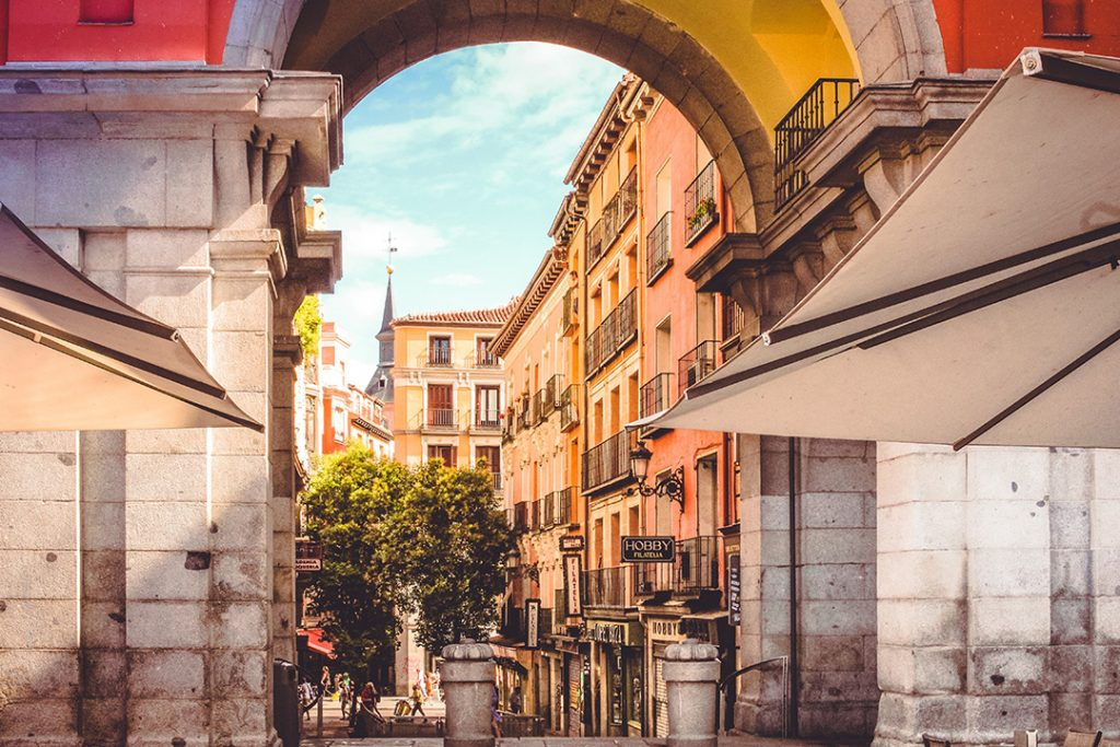 A square peaking through an archway in Madrid, Spain