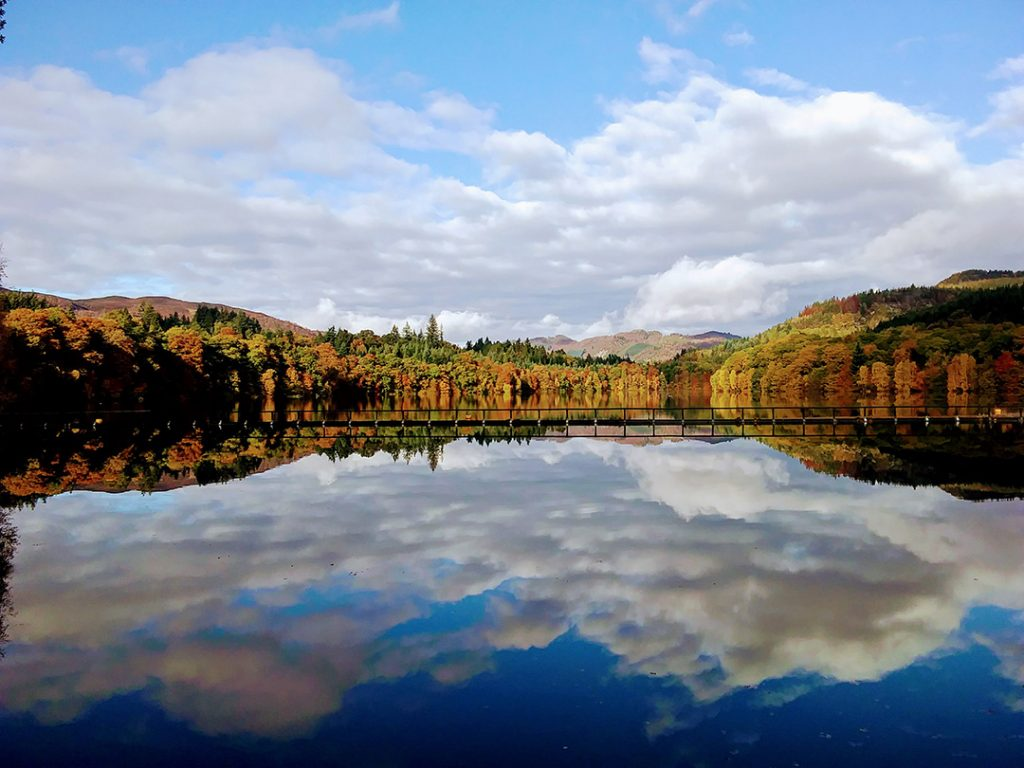 A lake reflecting the clouds and autumn color trees in Perthshire, Scotland