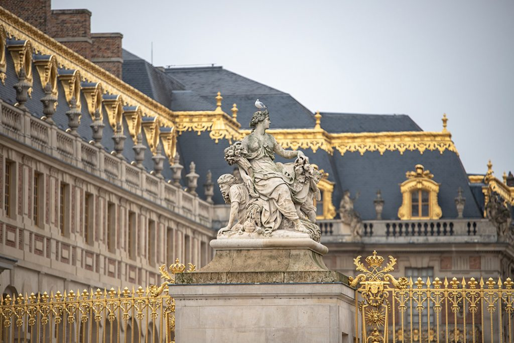 a statue and golden gates of versailles, france