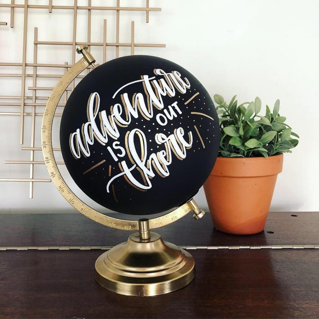 """A black painted globe that says """"Adventure is out there"""" - one of the best travel gifts for her"""