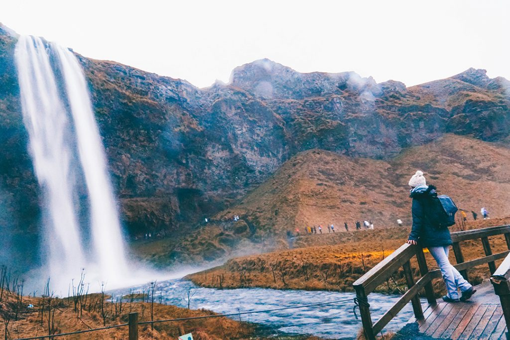 Addie standing on a bridge by Seljalandsfoss waterfall in iceland in December