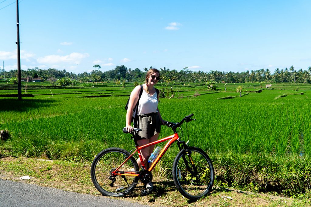 Addie with a bike in front of Ubud rice fields