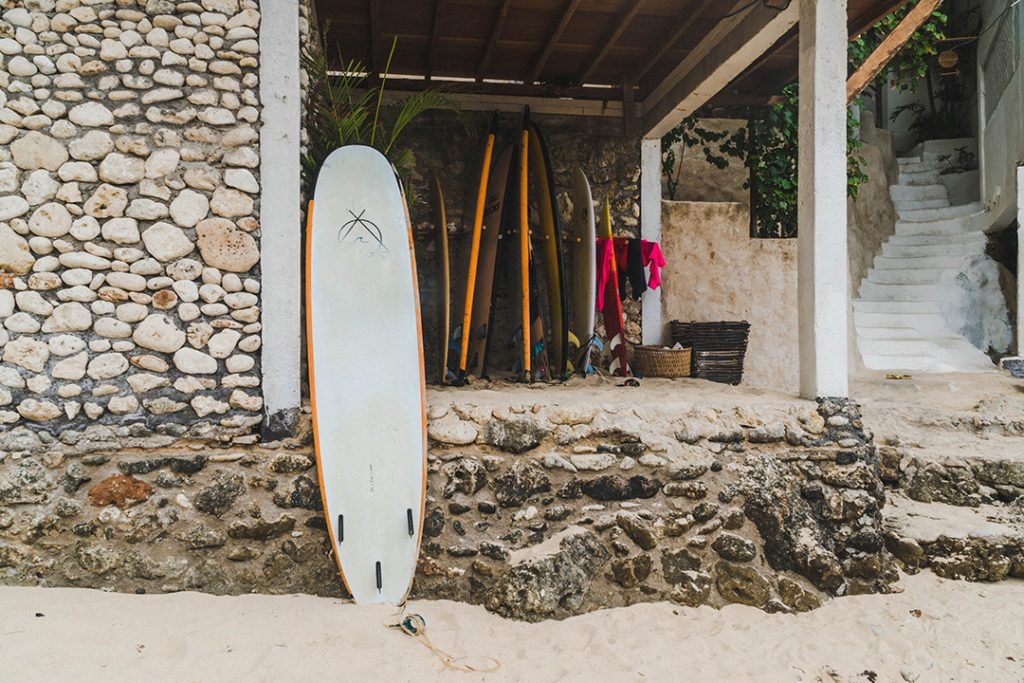 A surfboard leaned against a wall at a bali surf camp