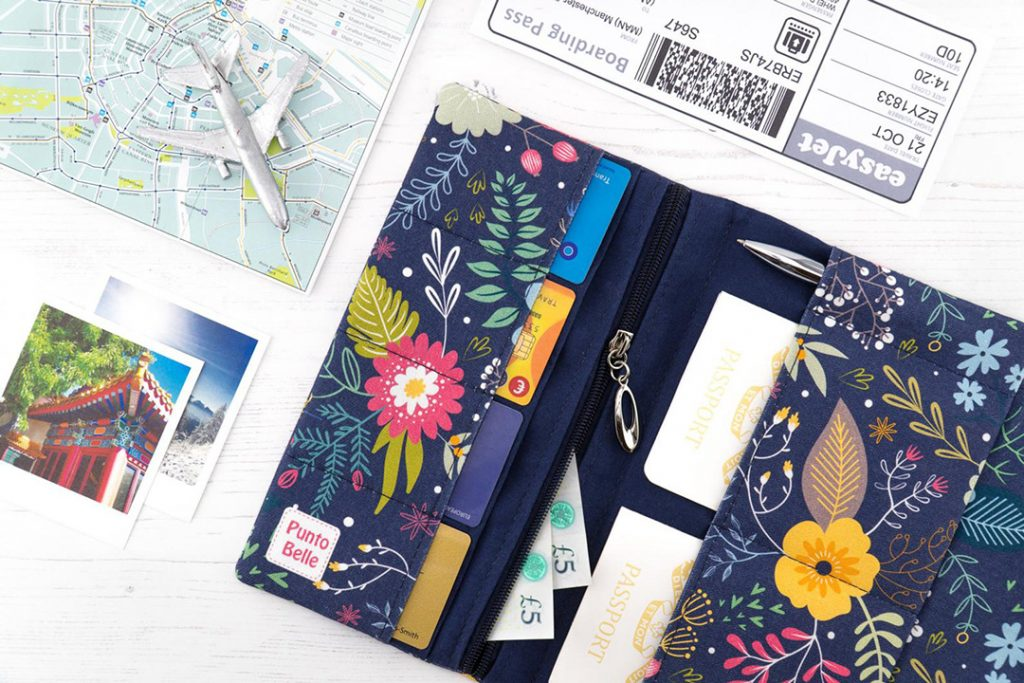 a flowery travel wallet among travel pictures, map, and plane ticket