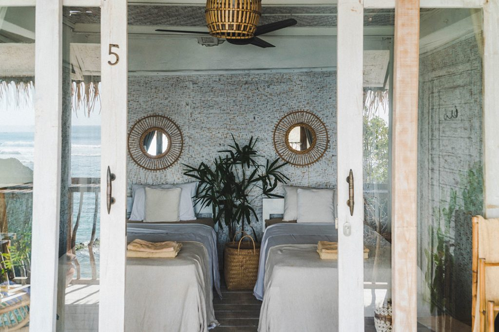 Sliding glass doors opening to two white-blanketed twin beds - the most gorgeous accommodation at a bali surf camp ever!