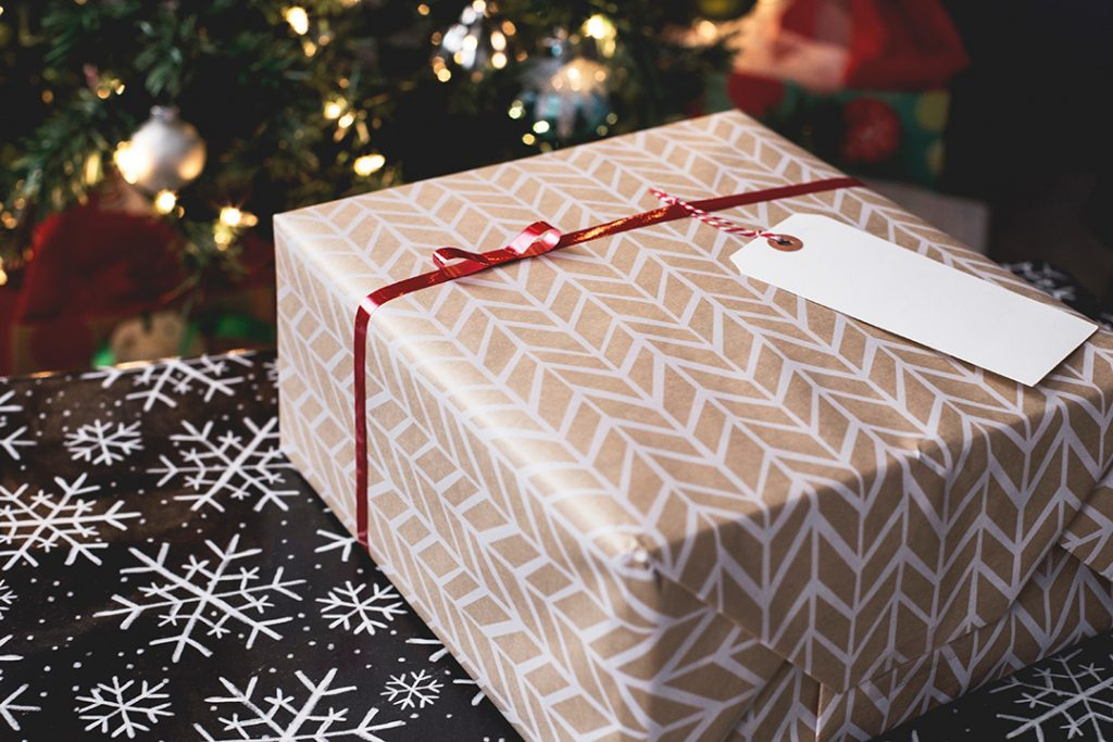 A gift box with fair isle print under a christmas tree - travel gifts for her