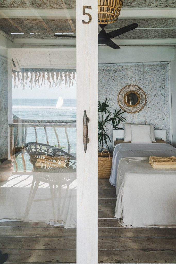 sliding glass door opening up to a bedroom at this bali surf camp