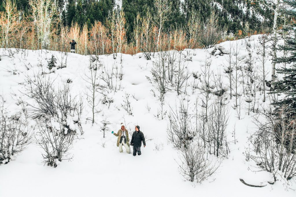 a man and woman knee-deep in snow in a forest in Aspen, Colorado, one of the most beautiful places to visit in winter in usa