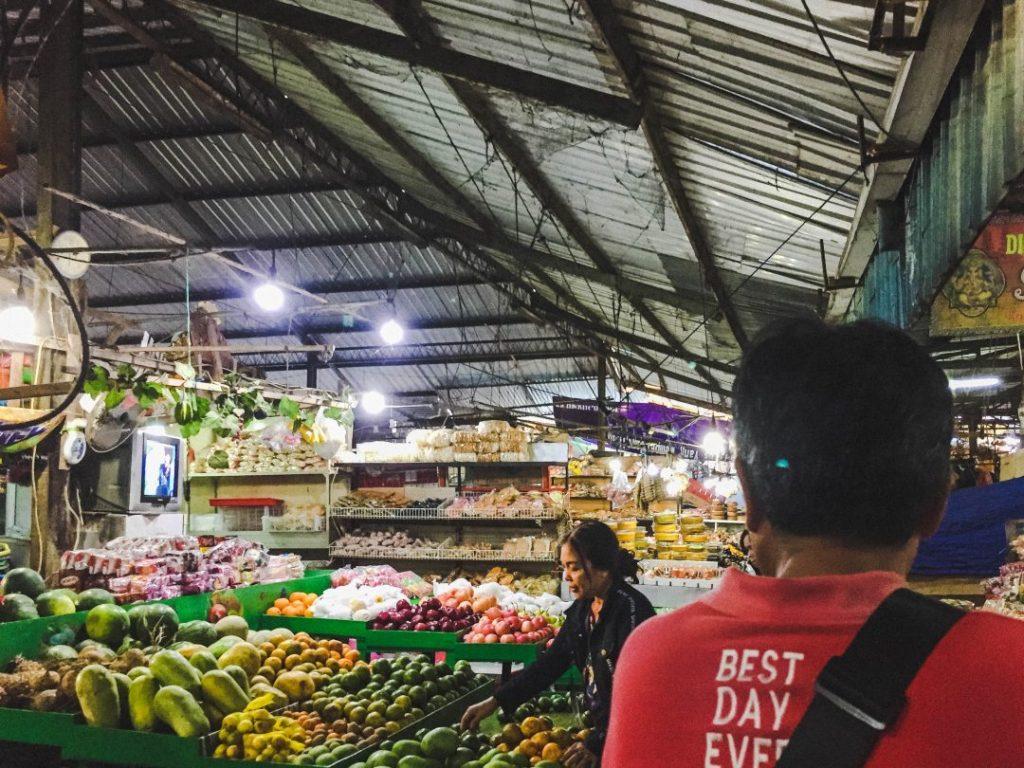 Urban Adventures guide walking through a local market during a Total Bali Food tour