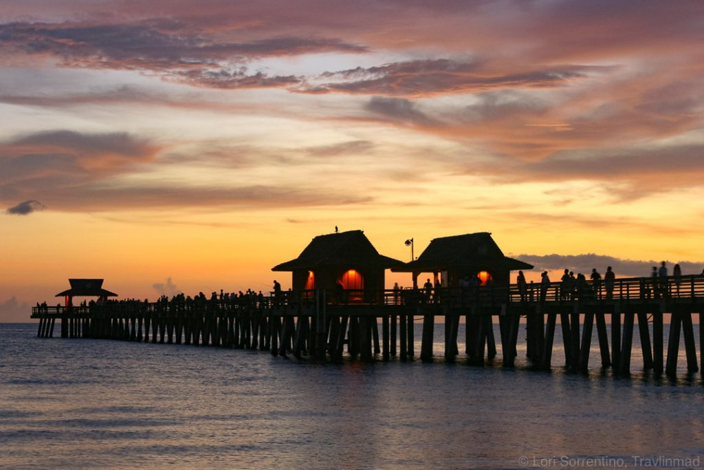 a colorful winter sunset behind a silhouetted pier in Naples, Florida