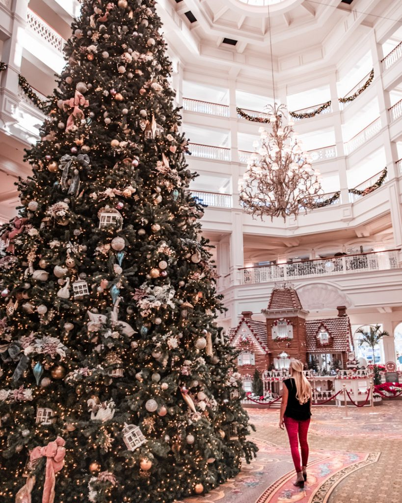 a woman standing looking up at a giant christmas tree in the lobby of a hotel in Orlando, Florida
