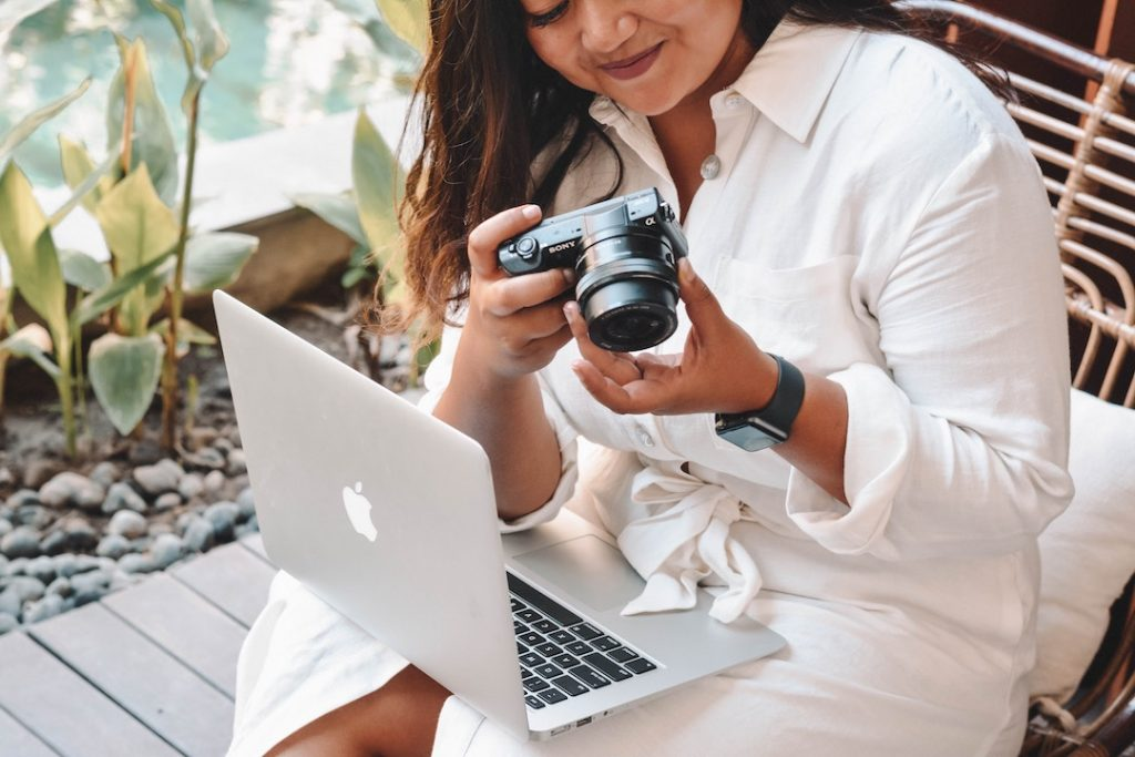 a woman in a white dress with a laptop and camera