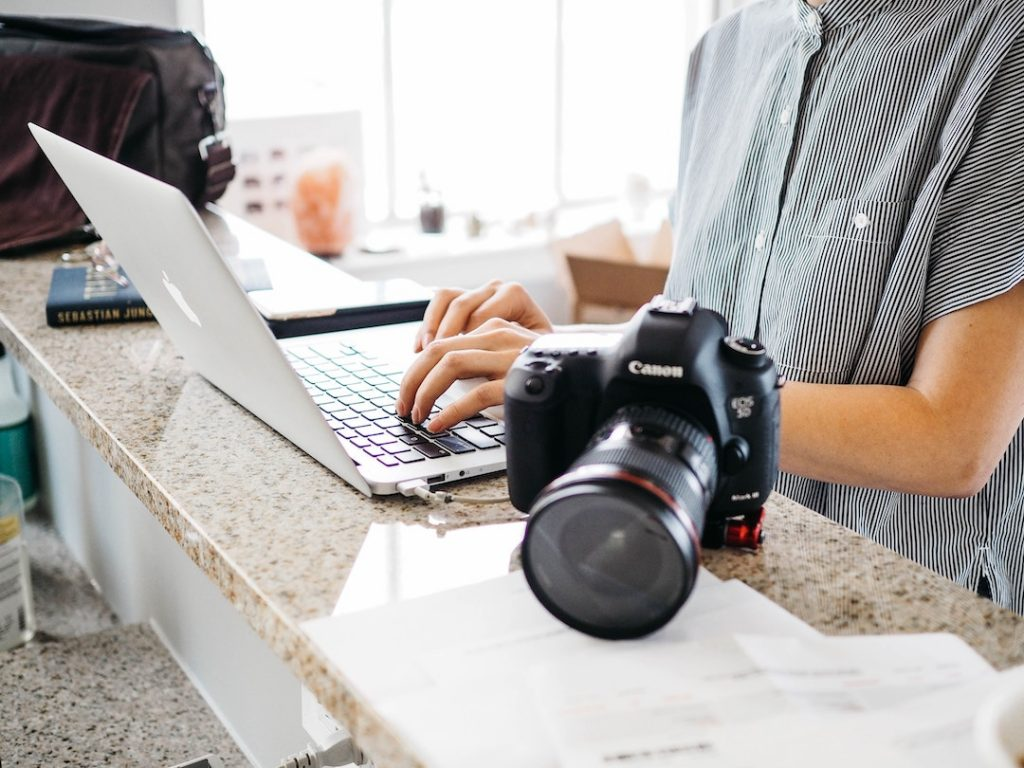 a person sitting at a counter with a laptop and camera