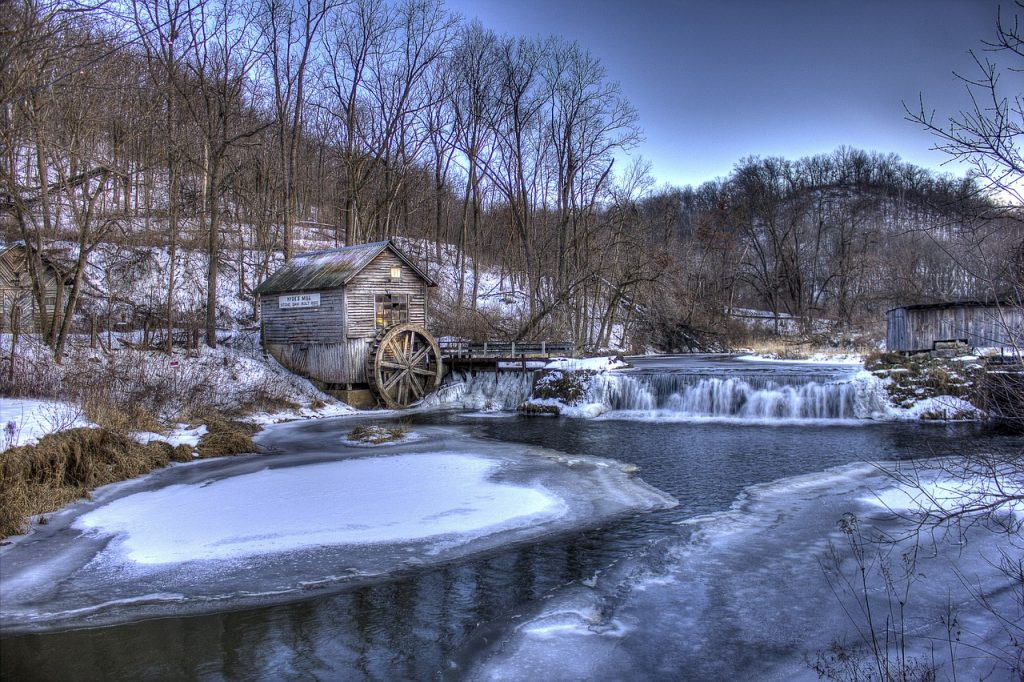 a small brown cabin with water wheel on a frozen over river in Wisconsin