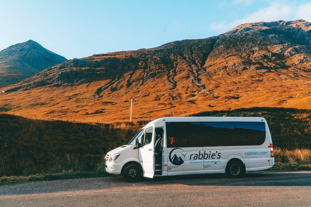 A Rabbie's minivan against a stunning highland hill on its isle of skye tour from edinburgh