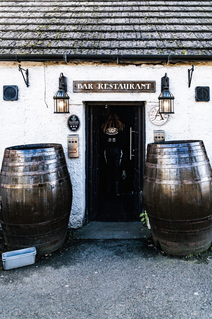 2 large barrels flanking the door of an inn