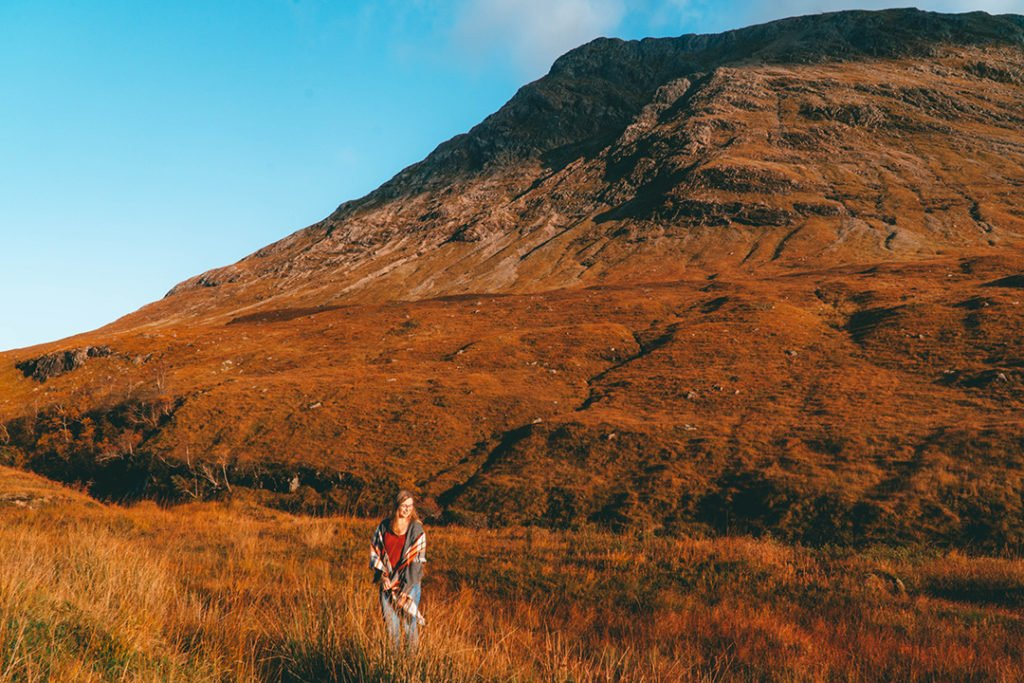 Addie standing in the grass in front of a mountain in Glen Etive