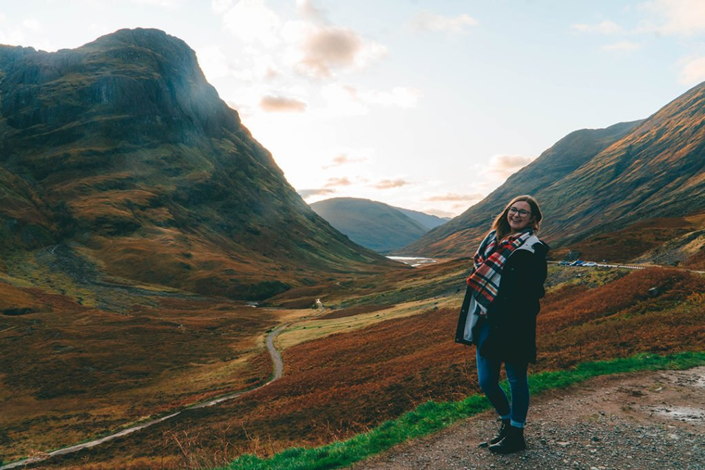 Addie standing in front of Glencoe, one of the best solo female travel destinations