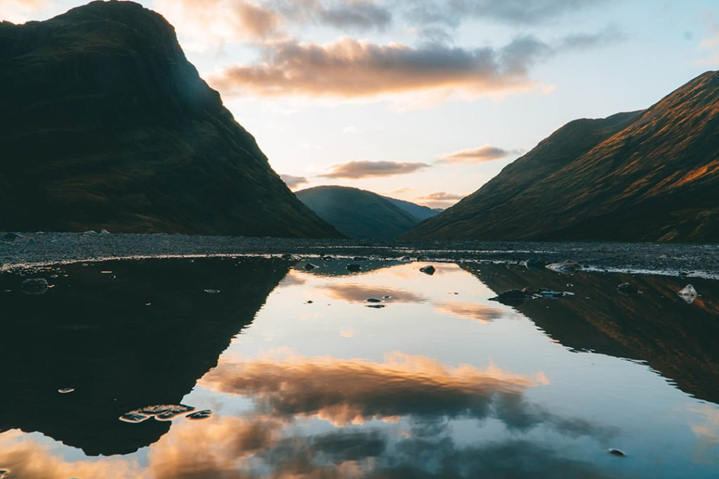 The mountains of glencoe reflected in a puddle. Glencoe is a must-see on any Highlands and Isle of Skye tour from Edinburgh