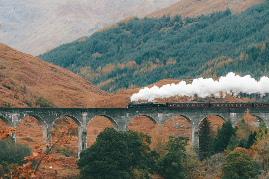 the jacobite steam train going over the glenfinnan viaduct with lots of steam