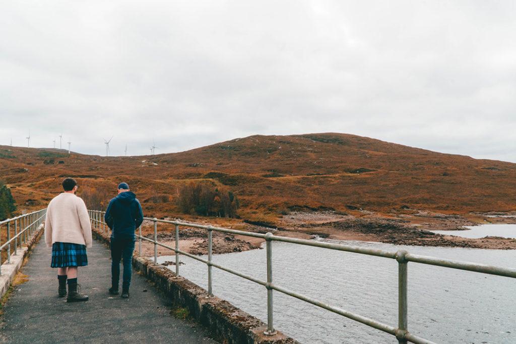 2 men walking over a dam