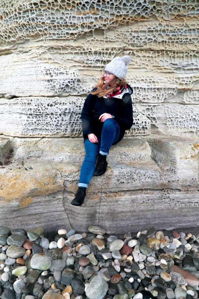 addie sitting on a cliff at elgol