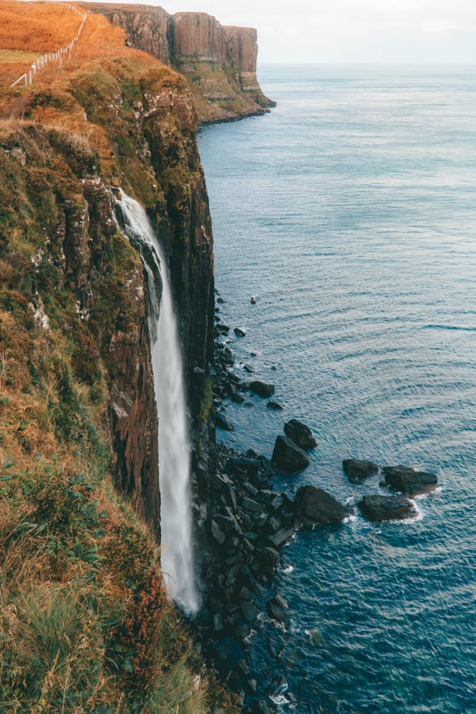 a waterfall cascading down a cliff - kilt rock, a stop on the Rabbie's isle of skye tour from Edinburgh