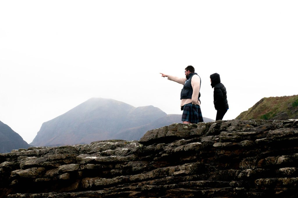two men - one in a kilt - standing on a cliff and pointing. the best guides on this isle of skye tour from edinburgh.