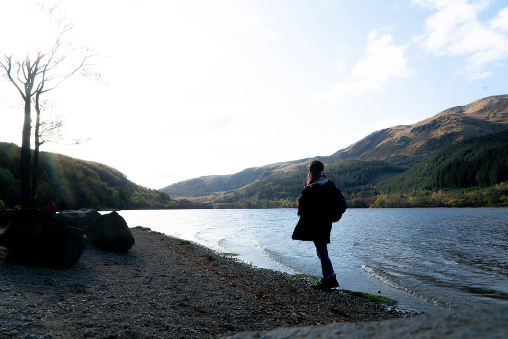 Addie standing on the rocky shores of Loch Lubnaig