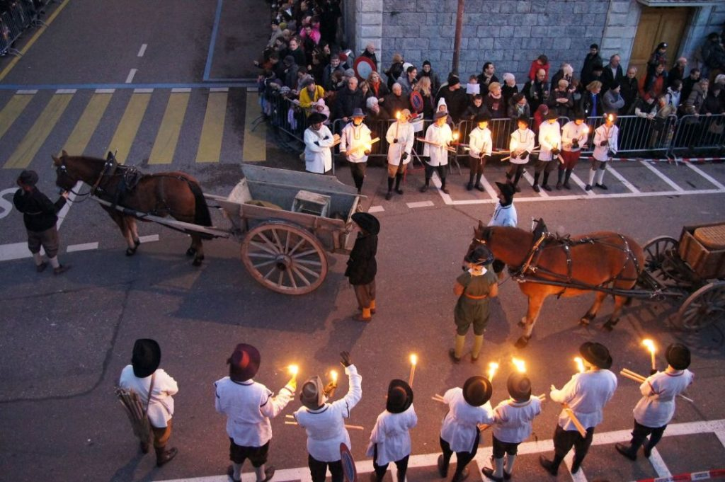 people in old-fashioned costumes holding candles as horses pulling carts go through the street in Geneva, one of the best places to visit in Europe in winter