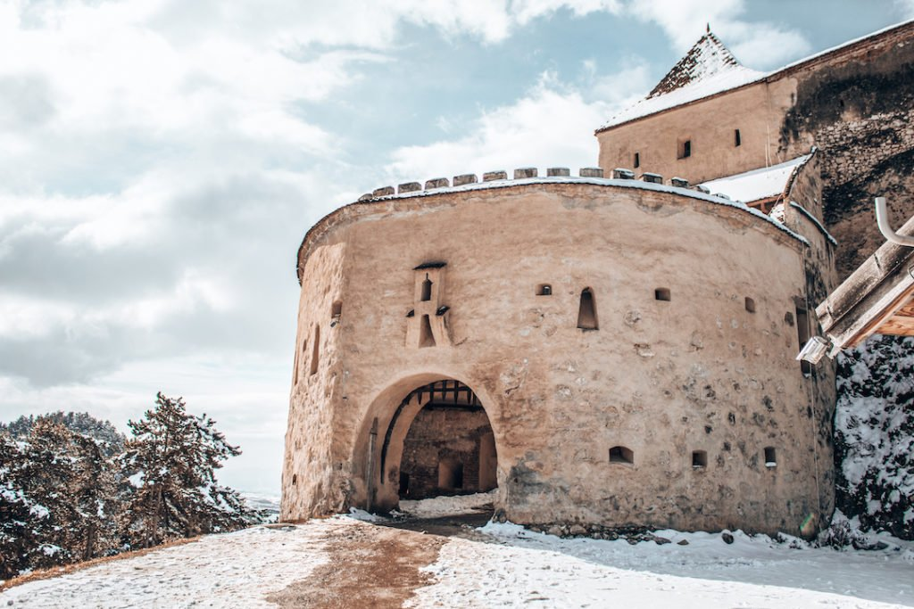 a castle dusted in snow in Romania, one of the best places to visit in Europe in winter