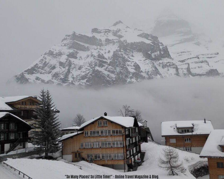 wooden houses covered with snow in front of a mountain in Murren, Switzerland