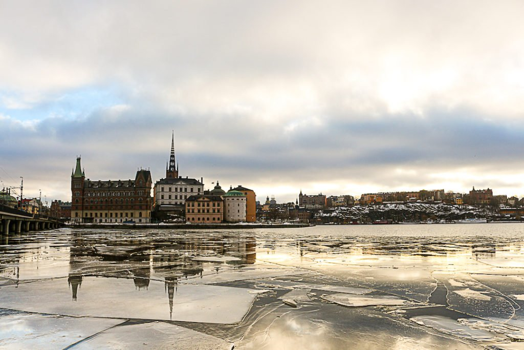 ice on a lake with buildings in the background in Stockholm, Sweden
