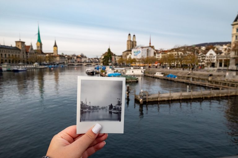 a hand holding up a polaroid of the zurich skyline in front of the skyline and river, one of the best places to visit in Europe in winter