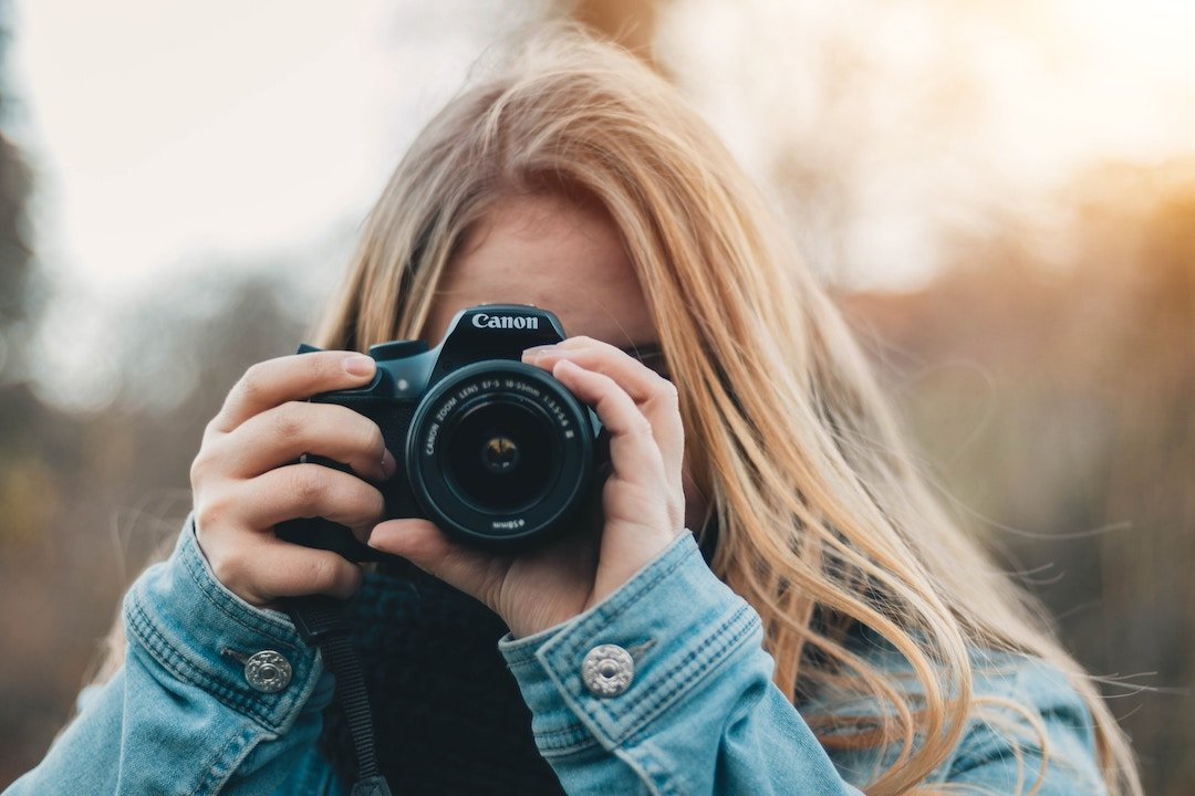 blonde girl holding a camera