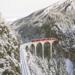 a train going over a viaduct in a snowy mountain landscape