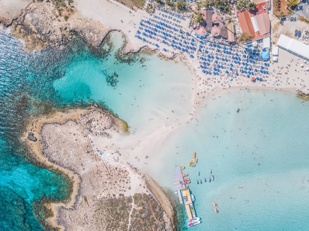 a photo from the air of vivid blue water and umbrellas on a beach in Cyprus