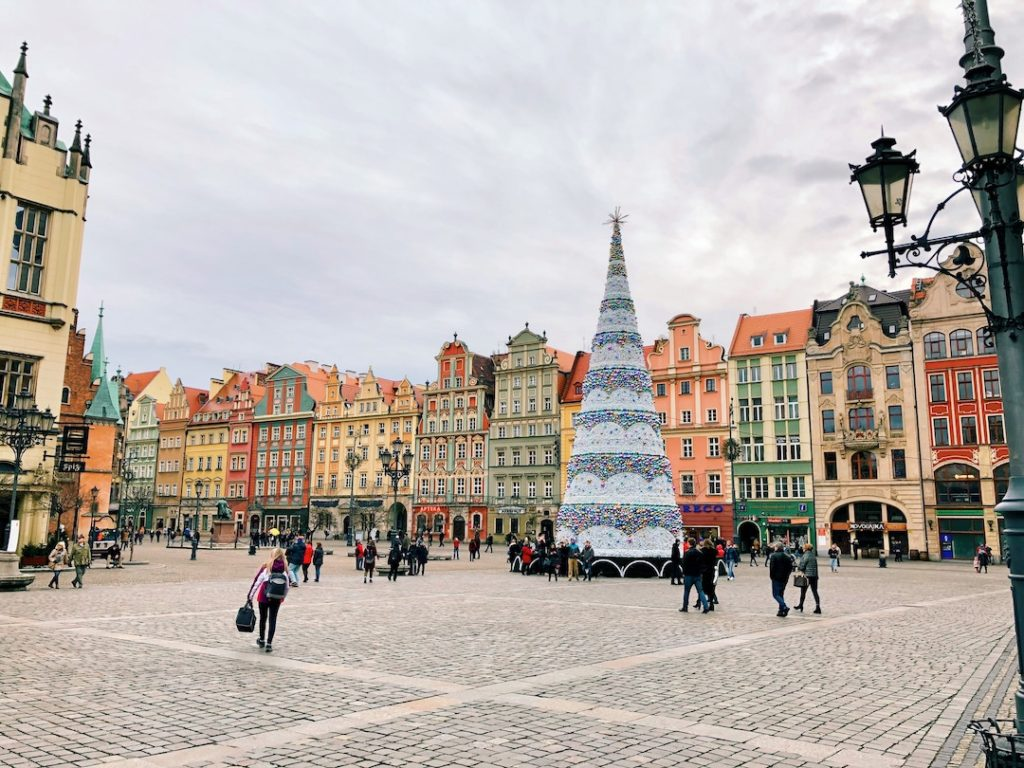 a christmas tree in a square of colorful houses on Wroclaw, Poland - one of the best places to visit in Europe in winter