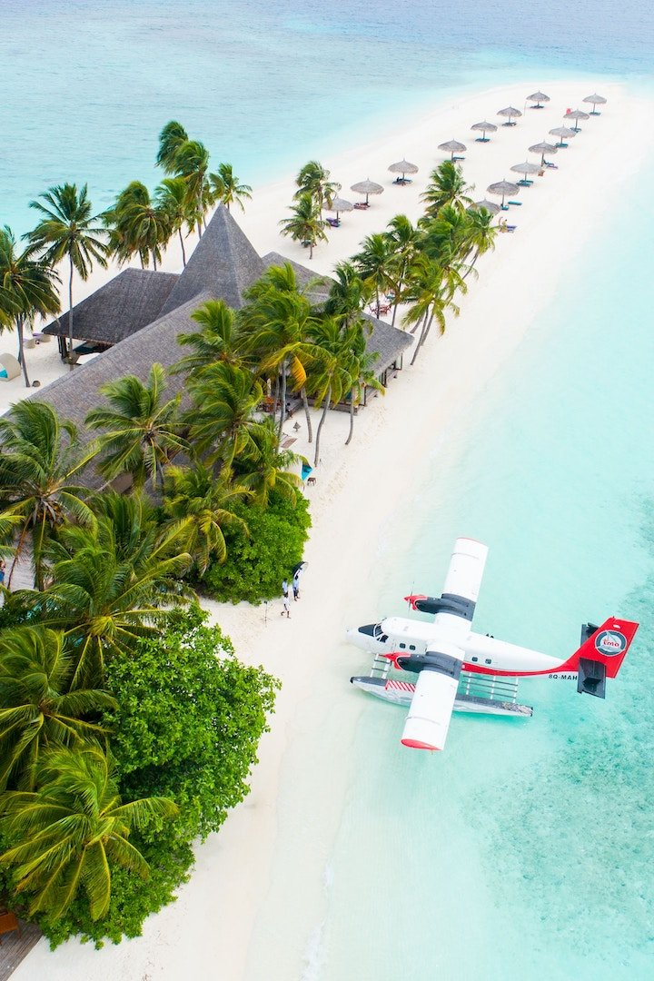 a small sea plane in very blue ocean on a beach with palm trees