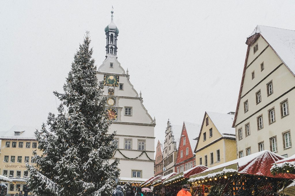 a large evergreen tree covered in snow in a colorful square at the Rothenburg ob der Tauber Christmas Market