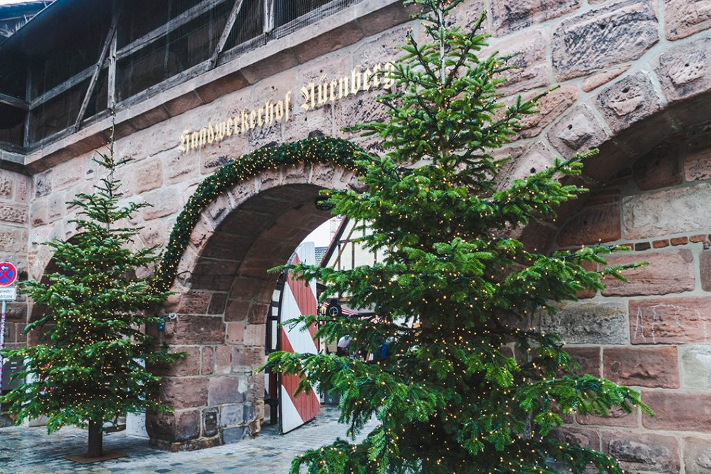 the entrance to the handwerkerhof flanked by christmas trees in nuremberg, germany