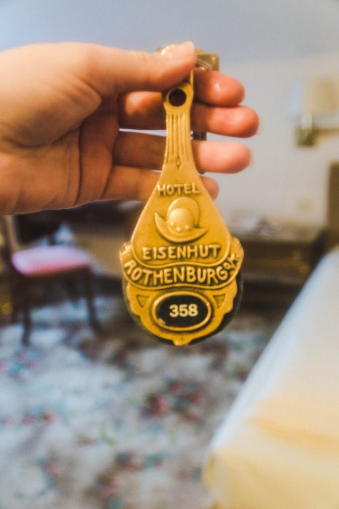 A hand holding up a gilded key for the Hotel Eisenhut
