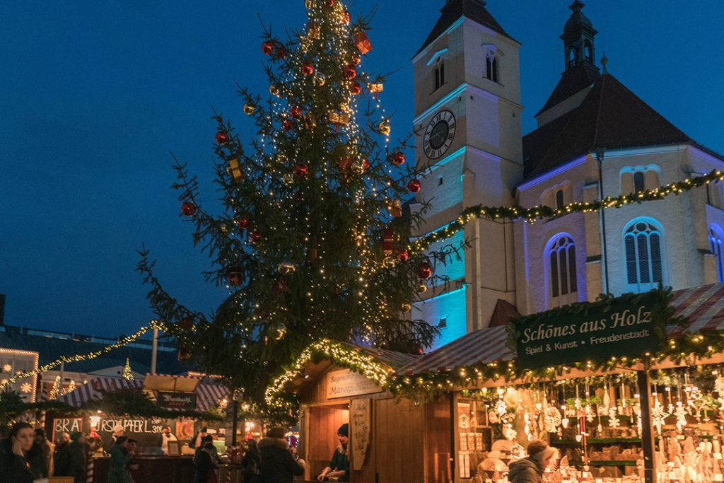 small wooden booths and a large christmas tree lit up at night