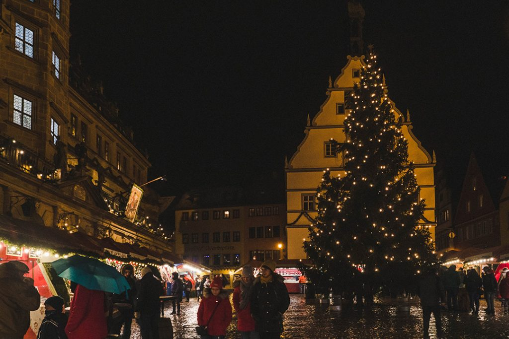 A large evergreen tree in the Rothenburg ob der Tauber Christmas market square at night