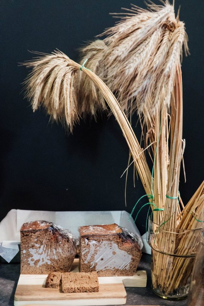 bread on a cutting board and wheat stalks in a vase
