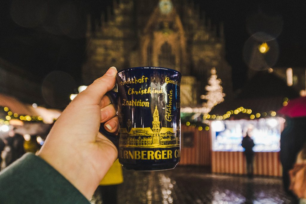 a hand holdin gup a gluhwein mug at the nuremberg christmas market, a great solo female travel destination