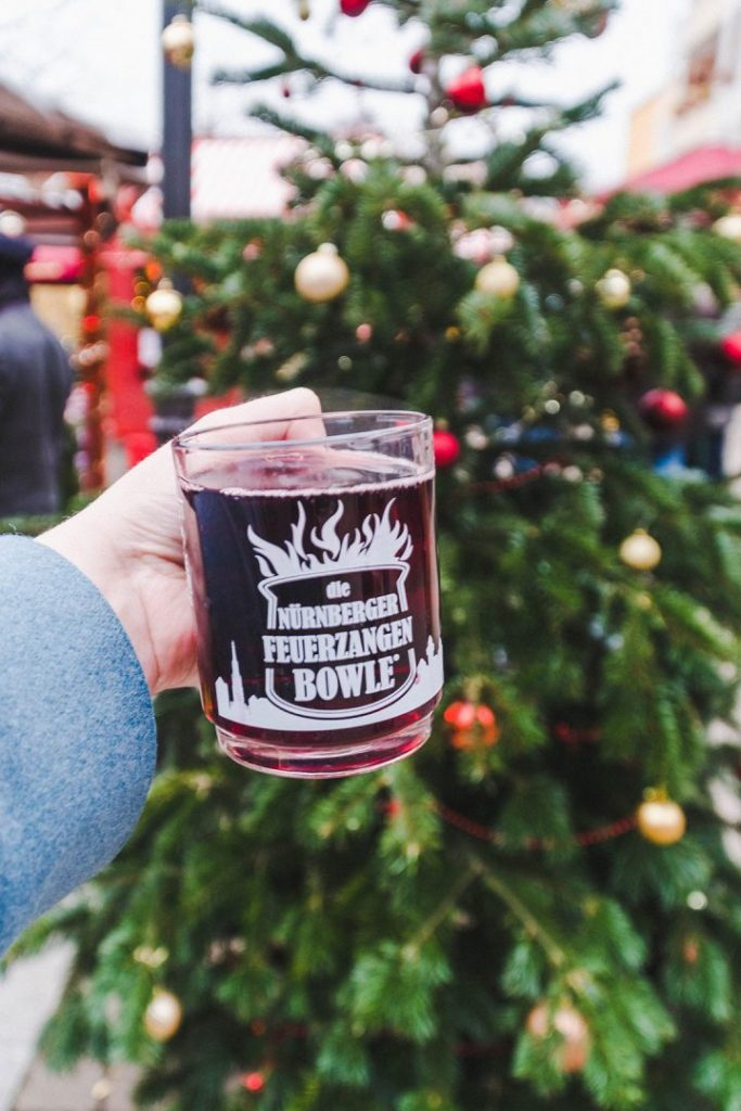 A hand holding up a mug of feuerzangenbowle