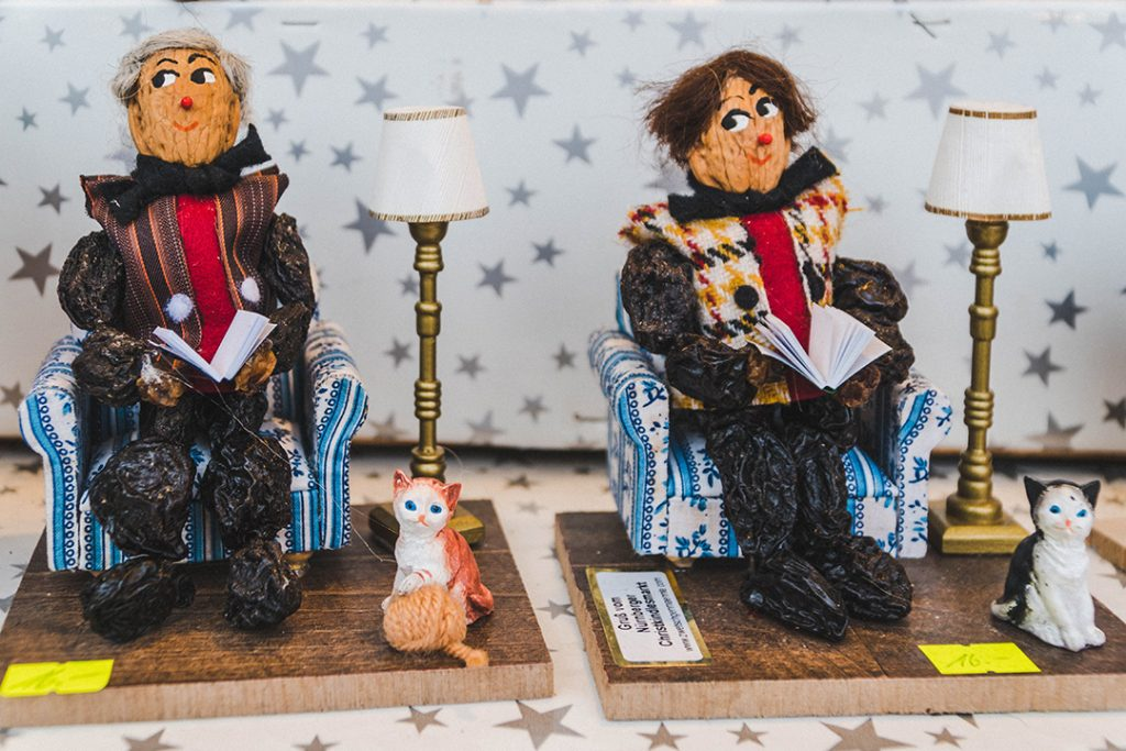 two zwetschkemanne (prune men) sitting in chairs and reading books